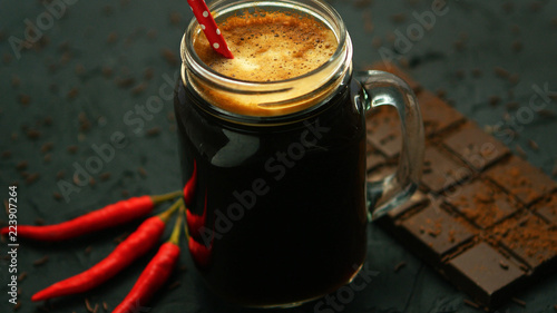 From above view of dark foamy drink in glass mug with chili and bar of chocolate placed near on gray background