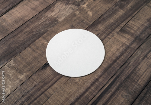 Blank beer coaster mockup on wood table background.