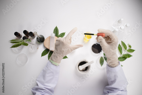 Fotografia  Scientist hand holding green leaf in glass cuvette on laboratory