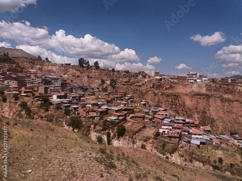 Papiers peints Cappuccino houses in located in slope, sky with white clouds in the background, location in the city of Cusco, peru.