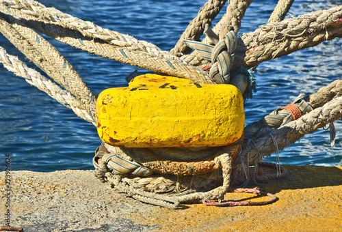 Fotografía  yellow mooring bollard with rope in the ship port