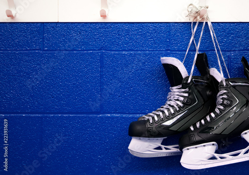 Hockey skates hanging over blue wall with copy space Wallpaper Mural