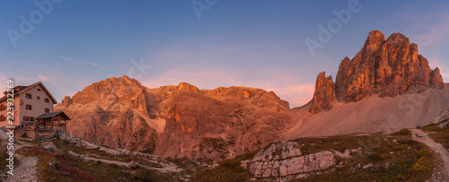 Tuinposter Awesome sunset panorama on Dolomite mountain hut with orange peaks background, South Tyrol, Italy