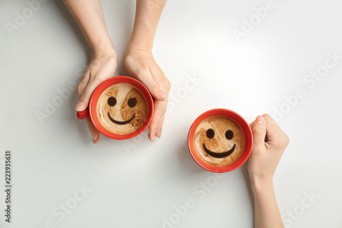 Young women with cups of delicious hot coffee on light background, top view