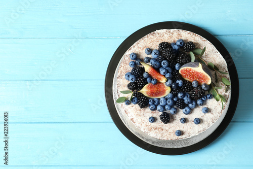 Delicious homemade cake with fresh berries and space for text on wooden table, top view