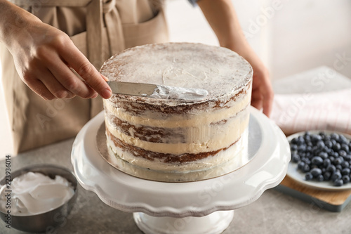 Fototapeta Woman decorating delicious cake with fresh cream on stand. Homemade pastry obraz