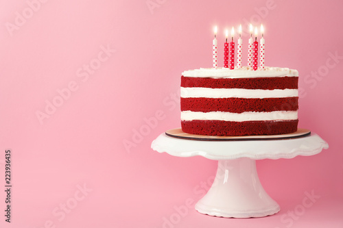 Delicious homemade red velvet cake with candles on pink background Fototapeta