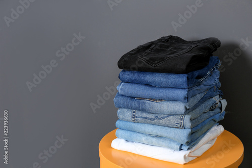 Fotografía  Stack of different jeans on  table against gray background