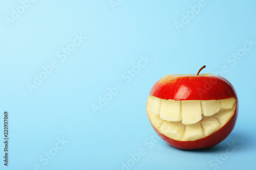 Fotografie, Obraz  Funny smiling apple on color background. Space for text