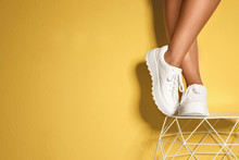 Woman In Stylish Sneakers Near Color Wall, Closeup. Space For Text