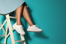 Woman In Stylish Sneakers On Ladder Near Color Wall, Closeup. Space For Text