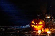 Carved Pumpkin Or Jack-o-lantern In Dark Barn, Halloween Holiday Celebration Concept
