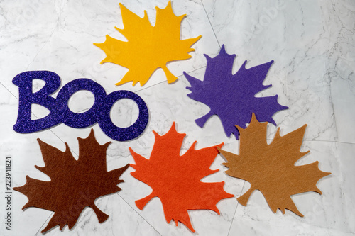 Fényképezés  Boo word for Halloween in glittery purple letters, colorful felt maple leaves