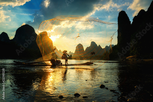 Canvas Prints Cappuccino Silhouette of Cormorant fisherman using net on the ancient bamboo boat