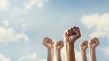 Peoples Raised Fist Air Fighting And Sunlight Effect, Competition, Teamwork Concept, Background Space For Text.