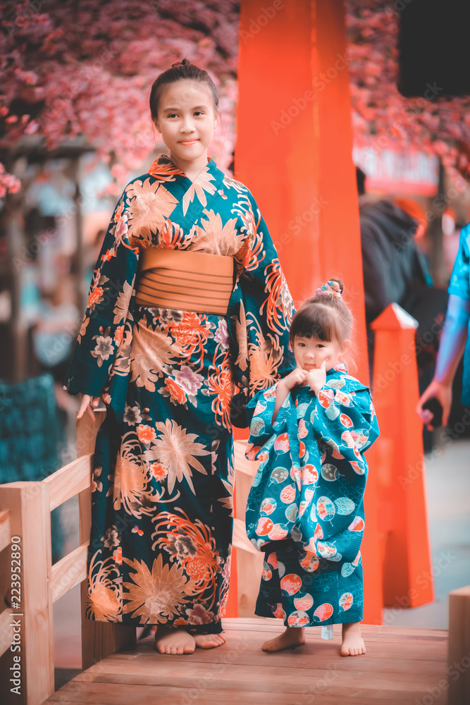 Fototapeta Sisters in japanese traditional kimono with cherry blossom