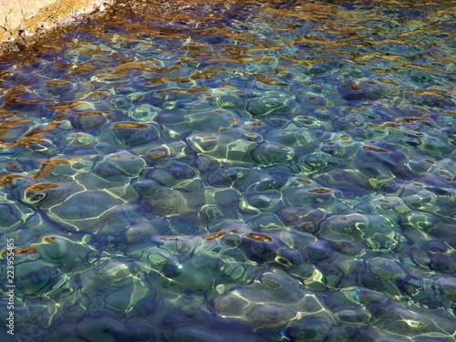 Fotografía  Clear blue sea ocean water over rocks