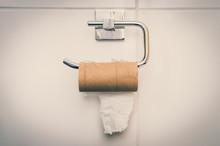 Empty Toilet Paper Roll In Public Restroom