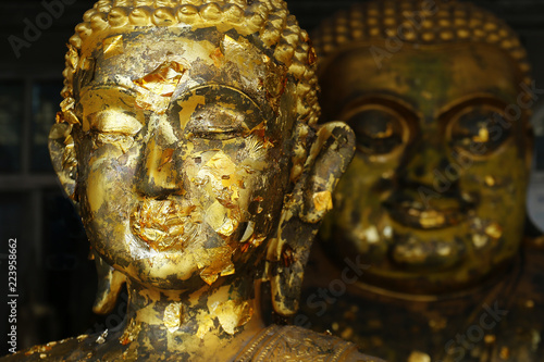 Tuinposter Boeddha head of statue of buddha with leaves of gold