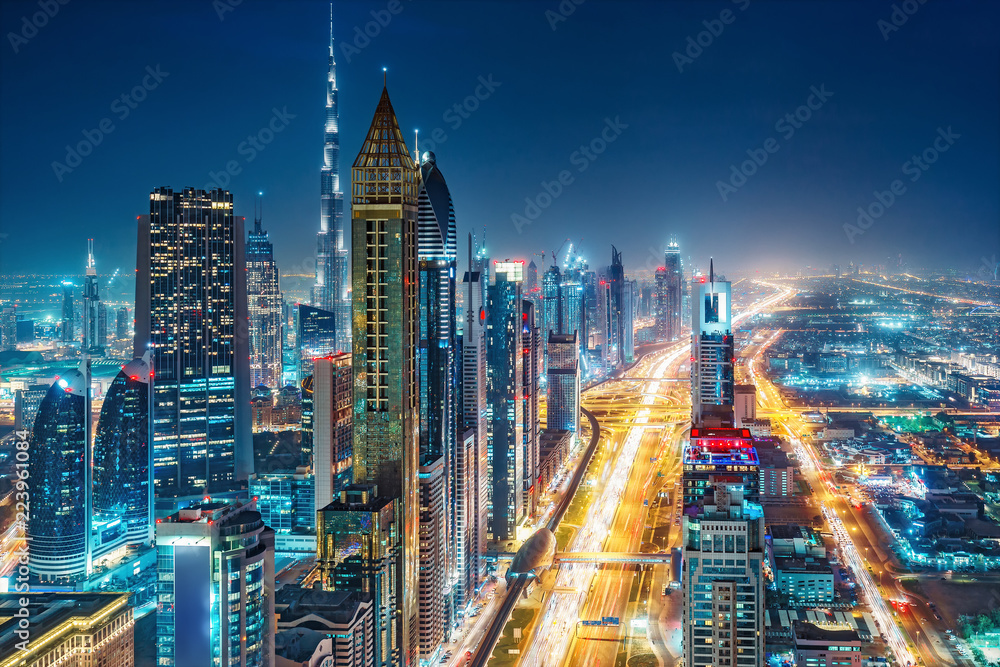 Fototapeta Spectacular urban skyline with colourful city illuminations. Aerial view on highways and skyscrapers of Dubai, United Arab Emirates.