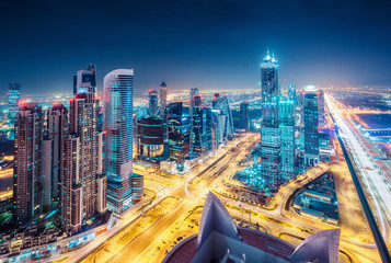 Fototapeta na wymiar Spectacular urban skyline with colourful city illuminations. Aerial view on highways and skyscrapers of Dubai, United Arab Emirates.