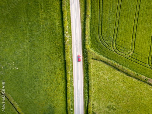 Photo Aerial view looking down on a rural road in the UK countryside with a car racing along it