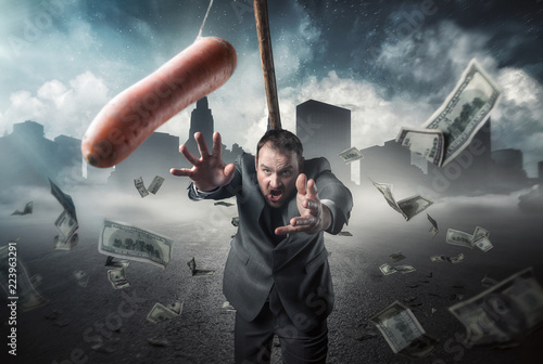 Fotografering  Businessman holding a carrot in a stick
