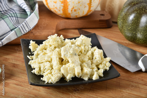 A dish of crumbled organic blue cheese on a cutting board with other ingredients