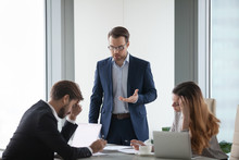 Angry Male Worker Standing Talking To Colleagues Lecturing On Mistake In Documents Or Failed Project, Businessman Show Dissatisfaction To Business Partner During Negotiations Or Meeting In Office