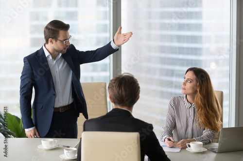 Mad male worker gesturing asking female colleague leave business meeting, angry Canvas Print