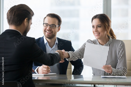 Photo Happy employers shake hand of male job candidate, congratulating with given position, satisfied HR managers happy to hire applicant handshake greeting at team