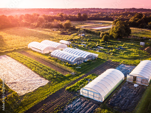 Fototapeta Drone aerial photography of an organic inner city farm taken at sun set in London. Polytunnels, agricultural buildings and farmland taken on the outskirts of a city. obraz