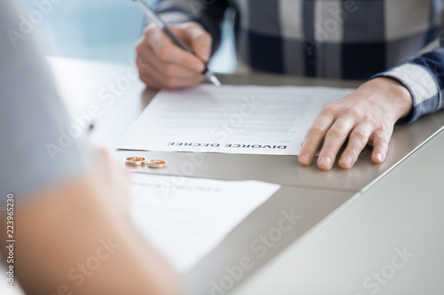 Close up of husband sign divorce decree ending relationships with wife, determined man put signature on document finalizing separation, breaking up or split officially Canvas Print