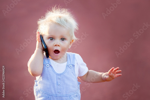 Cute baby boy playing with mobile phone in the park, digital technologies in the hands of a child