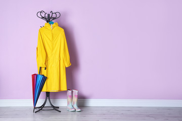 Umbrella, raincoat and gumboots near color wall with space for design