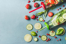 Detox Infused Water With Fruits, Berries Flavored With Fresh Herbs And Cucumber In Bottles With Drinking Straw, Top View