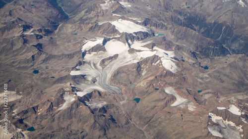 Flying over the European Alps during summer season. Landscape at the glaciers. Aerial view from the airplane window