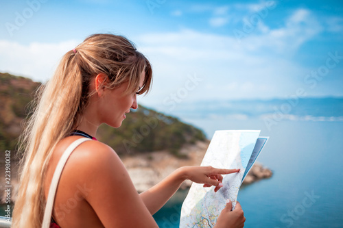 Fotografia  Happy young tourist woman with map on sea shore, travel lifestyle