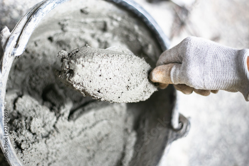 Photo  Cement or mortar, Cement powder with a trowel put on the brick at construction work