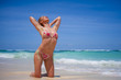 young sexy and happy blond girl in bikini having fun at tropical paradise beach enjoying Summer holidays trip posing playful and carefree in an amazing beautiful sea color