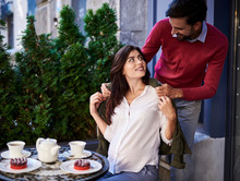 Pure Love. Portrait Of Loving Young Couple Spending Time In Outdoor Cafe. Smiling Pregnant Lady Sitting At The Table And Looking At Husband While He Giving Her Coat