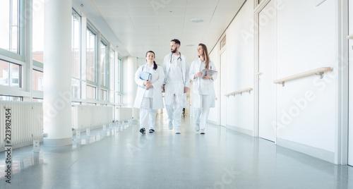 Fotografia Doctors, two women and a man, in hospital walking down the corridor