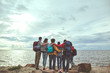 canvas print picture - Friendly hugs. Full length portrait of group of people from back making hug and looking at sea