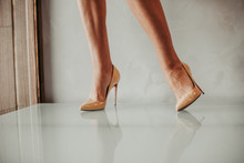 Close Up Female Legs In Bright Stylish Stiletto Shoes Going On White Floor With Their Reflection