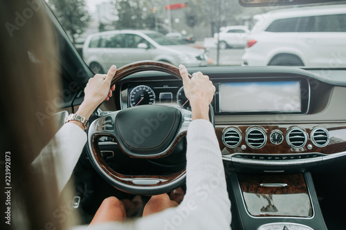 Foto op Plexiglas Fiets Close up woman hands keeping steering wheel while sitting in modern interior of vehicle. Girl driving car at street concept