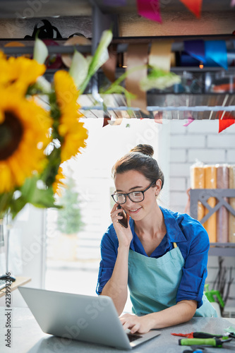 Fotografía  Portrait of modern young businesswoman speaking by phone and using laptop at cou