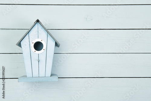 Stampa su Tela Blue wooden bird house on a blue wooden background with copy space