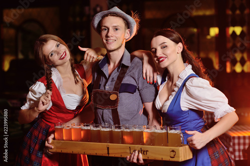 Fotografia people in Bavarian clothes with a beer board and glasses against a pub backgroun