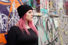 Young Alternative Woman With Pink Hair Piercings And Tattoos Leaning Against Graffiti Wall