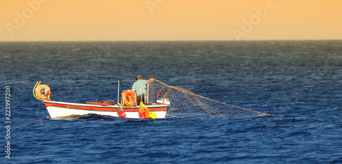 Greek fishermen fishing with net on the boat